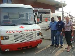 """Über den Verein """"Wir helfen Kindern weltweit"""" wurde der Krankenwagen für die Togo-Initiative finanziert: Vereinsgründer Frank Seibt (Mitte) übergibt das Fahrzeug an Anna Maria Klocke und Georges Batawila von """"Togo – Neuer Horizont""""."""
