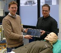 Torsten Seipel, Laerdal Medical (rechts im Bild), bei der Übergabe des SimMan 3G an Dr. Georg Breuer, Uni-Klinik Erlangen (links).
