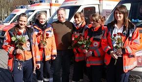 Wolfgang Maxeiner von der DRK-Rettungsdienst Rhein-Main-Taunus GmbH übergibt rote Rosen als Dankeschön für den starken Einsatz der starken Frauen.
