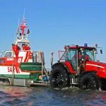 """Der Traktor schiebt den Trailer mit dem Seenotrettungsboot """"Butt"""" in die Ostsee. Foto: DGzRS"""