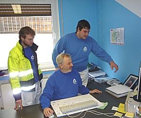 Ingo Porzel, den Leiter des Asklepios-Fahrdienstes, sitzend mit seinen Mitarbeitern Antonio Manelli (rechts) und Thomas Colell bei der Einsatzplanung.