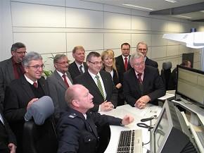 Auf dem Foto u.a.: Staatssekretär Roger Lewentz (2. v.l.), Landrat Dr. Alexander Saftig (5. vl.) Bürgermeisterin Marie-Theres Hammes-Rosenstein (6. v.l.) und Oberbürgermeister Prof. Dr. Joachim Hofmann-Göttig (2. v.r.), die sich die Technik eines Leitstellenarbeitsplatzes zeigen lassen.