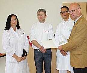 Landrat Stephan Loge (re.) übergibt den Zuwendungsbescheid an (v.l.n.r.:) Dr. med. Ariane Kalsow, Rettungsassistent Matthias Enders und Dr. med. Marc Redies.
