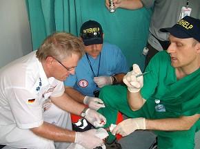 Haiti-Einsatz: Dr. Stefan Schindler (re.), Reinhold Klostermann (li.) und Bernhard Mandla versuchen den faulenden Finger eines Patienten zu retten. (Foto: Interhelp)