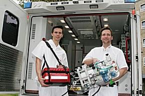 Leichtgewicht: Oliver Kowa, Leiter des DRK-Rettungsdienstes Düsseldorf und ein Mitarbeiter vor einem DRK-Intensivmobil mit der Life-Box des Herzzentrums der Uniklinik Düsseldorf  (Foto: Uni Düsseldorf)