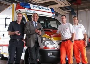 Der Leiter der Feuerwehr Bremerhaven Jens Cordes und Dezernent  der Feuerwehr Stadtrat Jörn Hoffmann mit einem Digitalfunkgerät mit Not- ruffunktion in der Hand sowie die Rettungsassistenten Maik Niederkrome  und Rainer Rogel vor einem der neuen Rettungsfahrzeuge mit Rundum- Kameraüberwachung. (Foto: BF Bremerhaven)