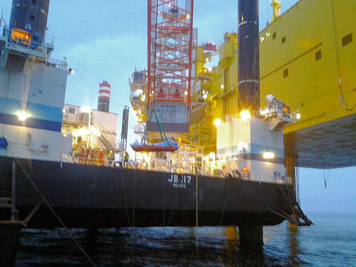 """Das Errichterschiff """"JB 117"""" übergibt mit seinem Kran einen schwer verletzten Offshore-Windpark-Arbeiter an den Seenotkreuzer """"Alfried Krupp"""". Foto: DGzRS"""