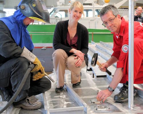 Schiffbauingenieurin Jessica Bröring (Mitte) legt eine Jubiläumsmedaille der DGzRS in eine Vertiefung im Hauptdeck des Neubaus. Foto: DGzRS