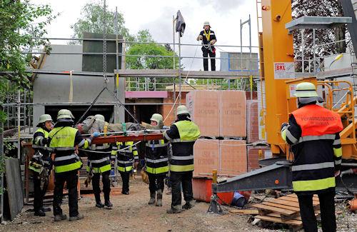 Ein verletzter Bauarbeiter wird mit Hilfe des Baukrans aus dem Unfallbereich gehoben. Foto: BF München