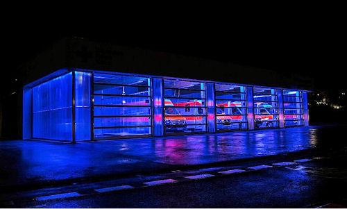 Bei Dunkelheit wird der Bau zum Blickfang. Denn dann erscheint er in vollem Neonblau. Foto: Alpha Deuren