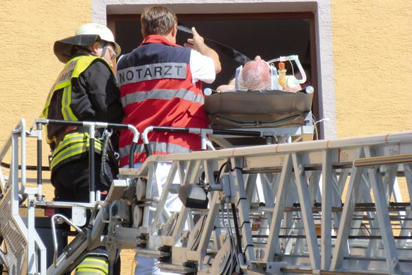 Beim Patiententransport mittels Drehleiter wird der Betroffene immer vom Notarzt – normalerweise mit Helm – begleitet. Foto: Maximilian Kippnich
