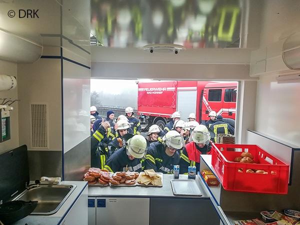 Feuerwehrleute bei der Speisen- und Getränkeausgabe am GW Verpflegung